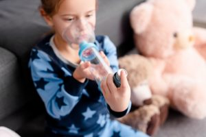 Young child with asthma sitting on a sofa using inhaler